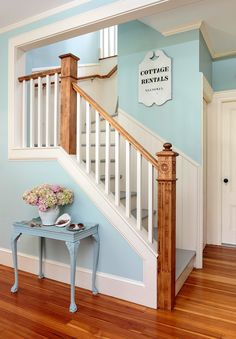 Here, wood newel posts and stair railings are left unpainted and refinished with a stain that lets the wood grain and carved details shine. #stairwayideas #remodel #stairways #stairwaymakeover #staircaseideas #stairwayrailingideas #bhg