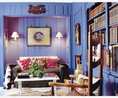 Relaxed library with purple walls, sconces, mossy green couch - Libby Cameron, LLC | Interior Design