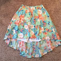 Candie's Floral High-Low Skirt Candie's Floral High-Low Skirt. Size Medium. Never worn! Excellent condition. Elastic waistband in back. Lined. I'm about 5'6 and the front of the skirt hits me right above the knee. Candie's Skirts High Low