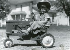 Little girl playing on her toy tractor, 1930s
