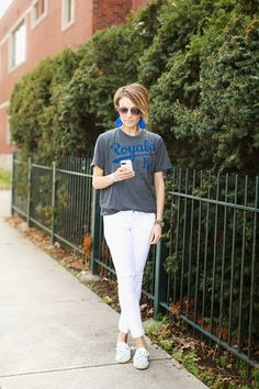 Super cute way baseball game outfit. Baseball t-shirt, white denim, sneakers, royal blue leather earrings. Stylish way to support your baseball team.