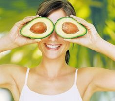 Six natural ways to increase derotonin - Young woman holding halved avocado over eyes, smiling, close-up
