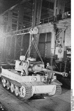 Panzer factory continues producing tanks in 1944. Here, the turret is lowered on the chassis, with two mechanics, one of them in a fedora hat, fine tuning the installation apparently moving this super heavy slab of steel by hand. Despite massive damage because of Allied bombing, German heavy industry, under the prodding of Albert Speer, continued to produce heavy weapons until the very last days of the war.