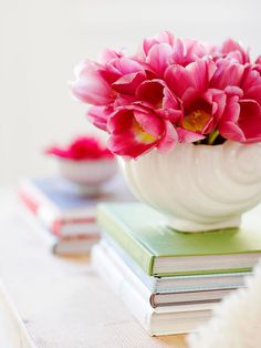 Coffee Table Collectables  Stacked books in bright colors that match the color palette create a pedestal for beautiful spring flowers and other home accessories