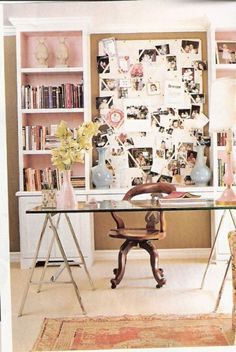 An office with carved wood chair, glass and metal desk.  Soft pink accents the back of the bookcases