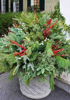 Evergreens, branches, berries, lights, seedpods, dried hydrangea blooms, and dried eucalyptus create a lively display in an outdoor planter. - Traditional Home ® / Photo: Courtesy of Mariani Landscape