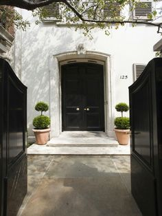 Black doors and topiaries welcome you to Bunny Mellon's Upper East Side townhouse. Now for sale.