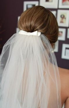 Veil with a bow, but pinned to the side, just off centre like a hat!