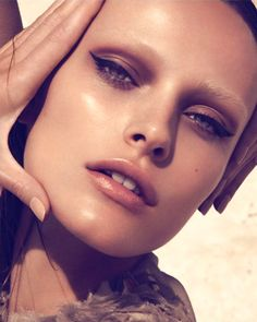 Nude lip, bronze complexion, winged liner.