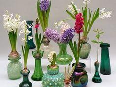 Kleurrijke verzameling hyacintenvaasjes in groene tinten, bovenop liggen bloeiende hyacintenbollen, tentoonstelling Patricia Coccoris in Arboretum Kalmthout 2015.