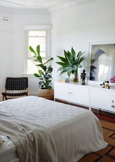 White bedroom with mid-century black woven chair and plants via @thouswellblog