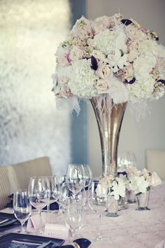 Florals in a metallic trumpet vase for the centerpiece