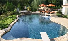 Lounge on your chairs sitting on a sun shelf. Stone raised spa with step spillover to a Pebble Tec pool. | Yelp