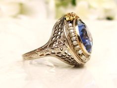 A fabulous antique engagement ring artfully crafted of a beautiful synthetic blue sapphire and 14k white gold with yellow gold ribbon and