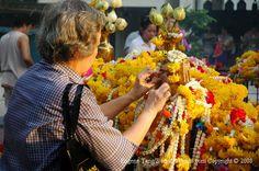 Four-Faced Buddha of  Erawan Shrine- Devotee make an offering using gold leaf. #shrines