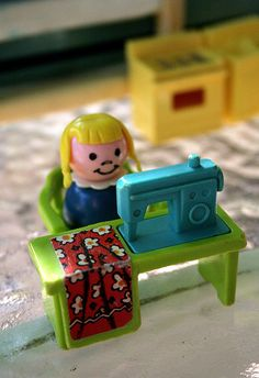 Fisher-Price Sewing Machine - photo by Nikki (lolie jane), via Flickr;  This little girl must want to show off her machine because she is sitting behind it.
