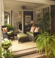 Living room on a porch with dark gray wicker patio furniture and lime green cushions and fabric