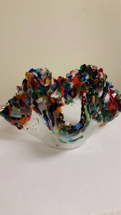 This fused glass candle holder is one Of a kind. The base is transparent glass with specs of colored glass shards. The top is adorned with multi