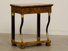 This beautiful console is made from burl walnut. It has the classic black columns associated with Biedermeier.