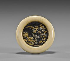 Antique Carved Ivory Kagamibuta Netsuke Antique ivory kagamibuta manju netsuke; ivory with circular bronze and soft metal plaque depicting a scene in relief of a crane standing among rockery and flowers, 19th Century