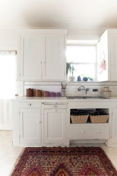 country-kitchen-with-kilim-design-sponge -- rug + cabinets + soft, vintage vibe.  My mother had those teak canisters.  They look fantastic in this space.