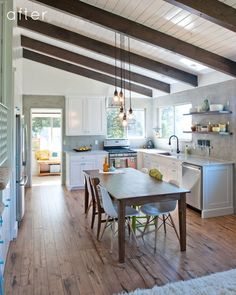 what's not to love about this kitchen? Exposed beams. Brights and airy. Table made from reclaimed barn boards. That light fixture! The gray plaster walls. Blue knobs. *sigh*. Even more impressive when you see the before picture and find out that the owners did the reno themselves for 15K in 3 weeks.