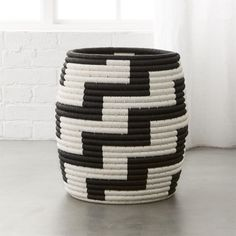 Shop Tatum Black and White Basket.   Seagrass is twisted by hand into a crisp stair step pattern.  A very high-end look.  Tight weave creates a hiding spot for toys and remotes, but our favorite use has it holding a leafy indoor potted plant.