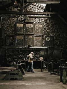 Dubreuil at work in his atelier, a converted sheep barn on the property. A collection of 19th-century ecclesiastical paintings from Belgium hang over the workbench.