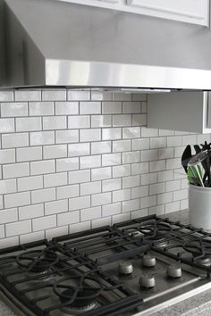 Gray grout with white subway tiles helps keep the kitchen from being whitewashed.