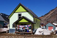 """Winter Laundry"" - A whimsical image of colorful winter laundry hanging on the clothesline of a bright yellow house. #Silverton #Colorado #photography #fineartamerica"