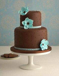 Chocolate blue wedding cake: This elegant chocolate cake is dotted with sugar pearls and decorated with stylish turquoise sugar flowers : Chocolate fudge cake, Amedei Toscano buttercream, handmade sugar ribbon trim and sugar flowers.
