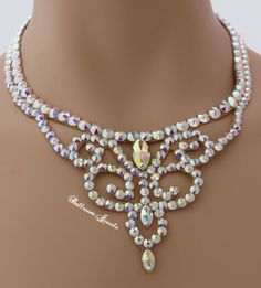 This necklace was created with Swarovski Elements aurora borealis clear crystals. The necklace is 3 inches at the widest point in front and tapers in the back for comfort. There are different shaped s