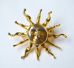 """Let the sunshine, let the sunshine in! With a beautiful vintage smiling sun-faced brooch. Its 3D item made of gold metal with silver reflections on the face and rays. It measures 6x5.5cm (2.36x2.16) and is made of gold and silver tone metal.  This brooch is in good vintage condition, with typical wear and tear for a previously owned item.  """"Make it simple, but significant."""" - Don Draper  The sun is the star at the centre of the Solar System and its not surprising it has been considered as a…"""