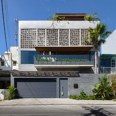 Concrete ventilation blocks integrated into the facade of this house in Ho Chi Minh City feature a geometric perforated pattern
