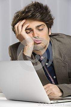 Portrait of sleeping overworked businessman in front of his laptop at work.