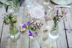 Kleine Vasen befüllt mit Blumen. Sieht einfach schön auf einer Tafel aus. Foto von Alex Gerrard Photography