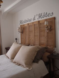 A headboard with a history- Provencal wooden shutters with vintage lights.