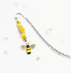 This is one of my new Busy Bee bookmark range, lovingly handmade in Northern Ireland. Ive used yellow beads and added diamonte spacers to compliment the sparkly wings of the bee, finished with aTibetan style marker.  The bookmark measures approximately 9 cm and comes presented in an organza bag,