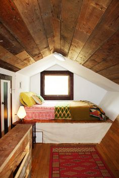 Raised bed in attic room. Love the wood paneling on ceiling, really completes the look :)