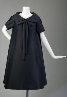 This is the trapeze dress. It was designed by Yves Saint Laurent in 1958 when he was designing for Dior. The A-line silhouette did not pronounce the waistline. This dress was created from black mohair.