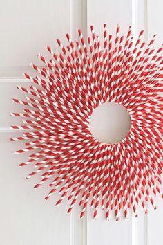 Una corona navideña original hecha de popotes blancos y rojos. Esta es la manualidad perfecta para diciembre y para ser original.