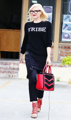 Gwen Stefani in a black sweater, dark denim overalls, red handbag, and open-toe boots