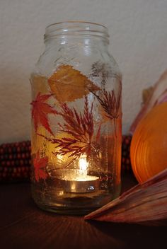 Mod Podge leaves onto a mason jar or other glass container