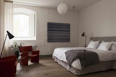 Hotel rooms are designed with custom bed frames and chairs, Le Klint Pendant Lights, and Rubn Hunter Floor Lamps.