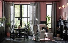 Obývací pokoj s velkými okny; různé tóny černé, světle fialové a šedozelené.