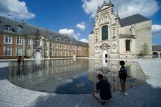 OMGEVING // averbode abbey square // thin plane of water creates a mirror for the bordering structures