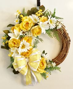 Yellow Roses, White Lilies, White Gerber Daisies & Wildflowers on a bed of green ferns & other greenery with a white & yellow/white checked bow