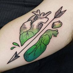 Anatomical heart tattoo crossed by an arrow.