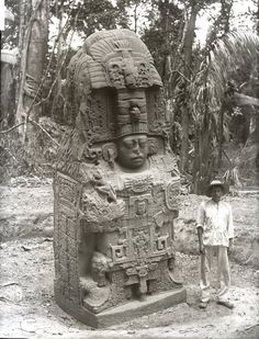 Man standing next to Stela K ; near the eastern border of the Great Plaza. Quiriguá, Guatemala. Quiriguá is an ancient Maya archaeological site along the lower Montagua river in south-eastern Guatemala. Photographed by Dr Alfred Percival Maudslay in 1894. -British Museum-