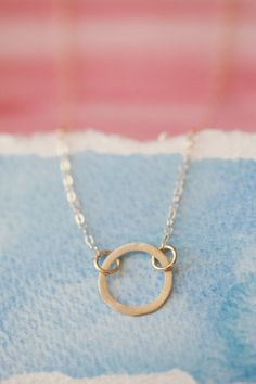 """A complete circle is strong, unstoppable and whole. This hand-crafted 10K gold ring represents the way our lives come together to create something more complete and more beautiful. With you I am whole. Ring measures 1/2"""" and is strung from gold-filled fine link chain."""